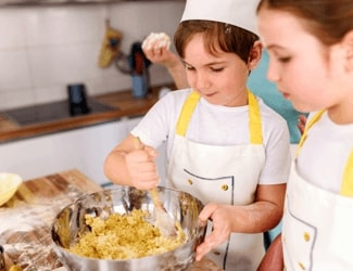 Kids mixing a batter during a cooking class.