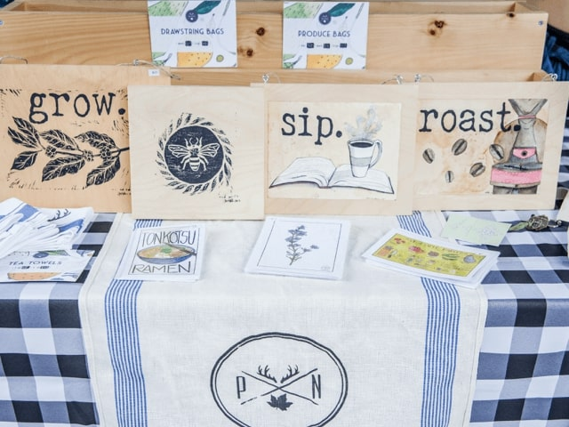 Painted signs and drawstring bags on display at an artisan's stall.
