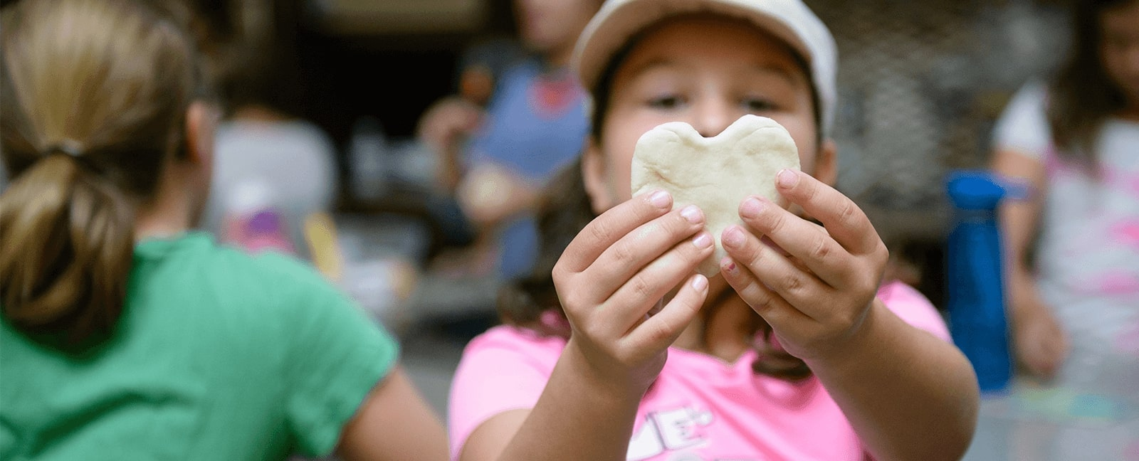 Child holding up a heart made out of dough in a Kids in the kitchen class at the Kitchener Market.