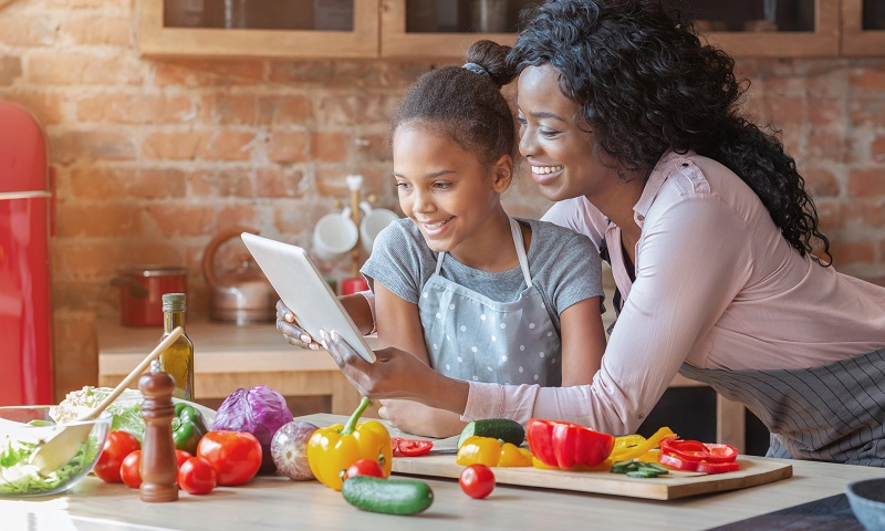 woman and child in kitchen with meal ingredients watching tablet