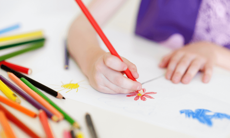 Child drawing on paper with a red pencil crayon.