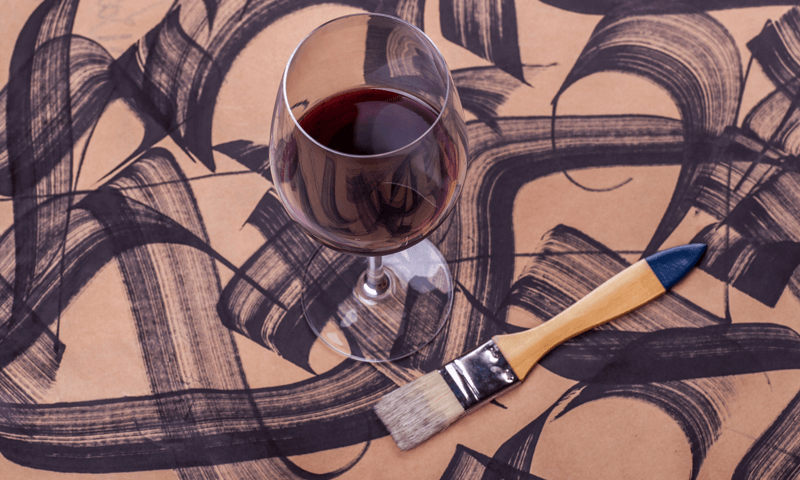 Wine sitting on a board beside a paint brush. There is messy paint on the board.